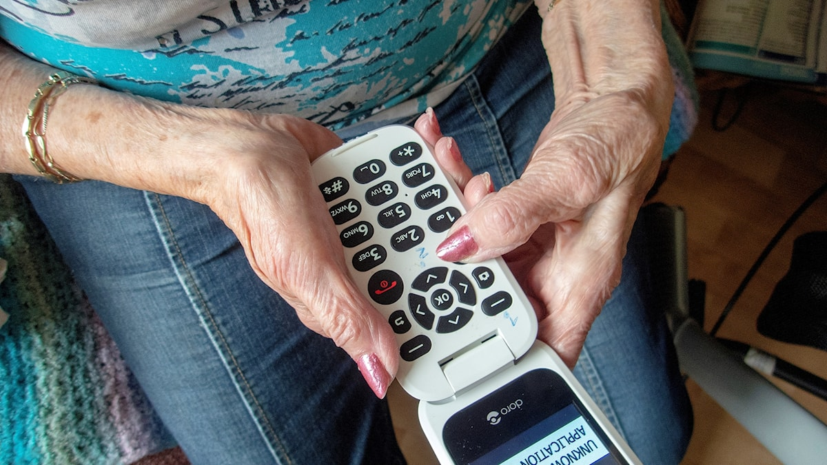 Elderly hands holding a phone.