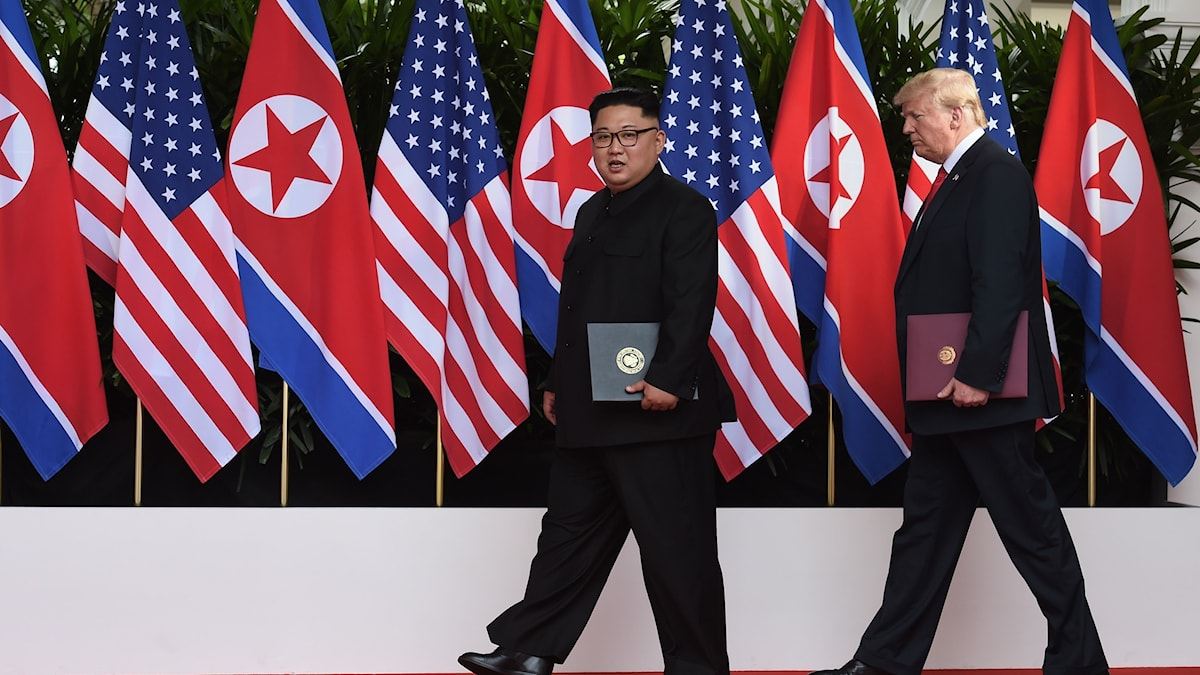 Kom Jong Un and Donald Trump walking in front of US and North Korean flags