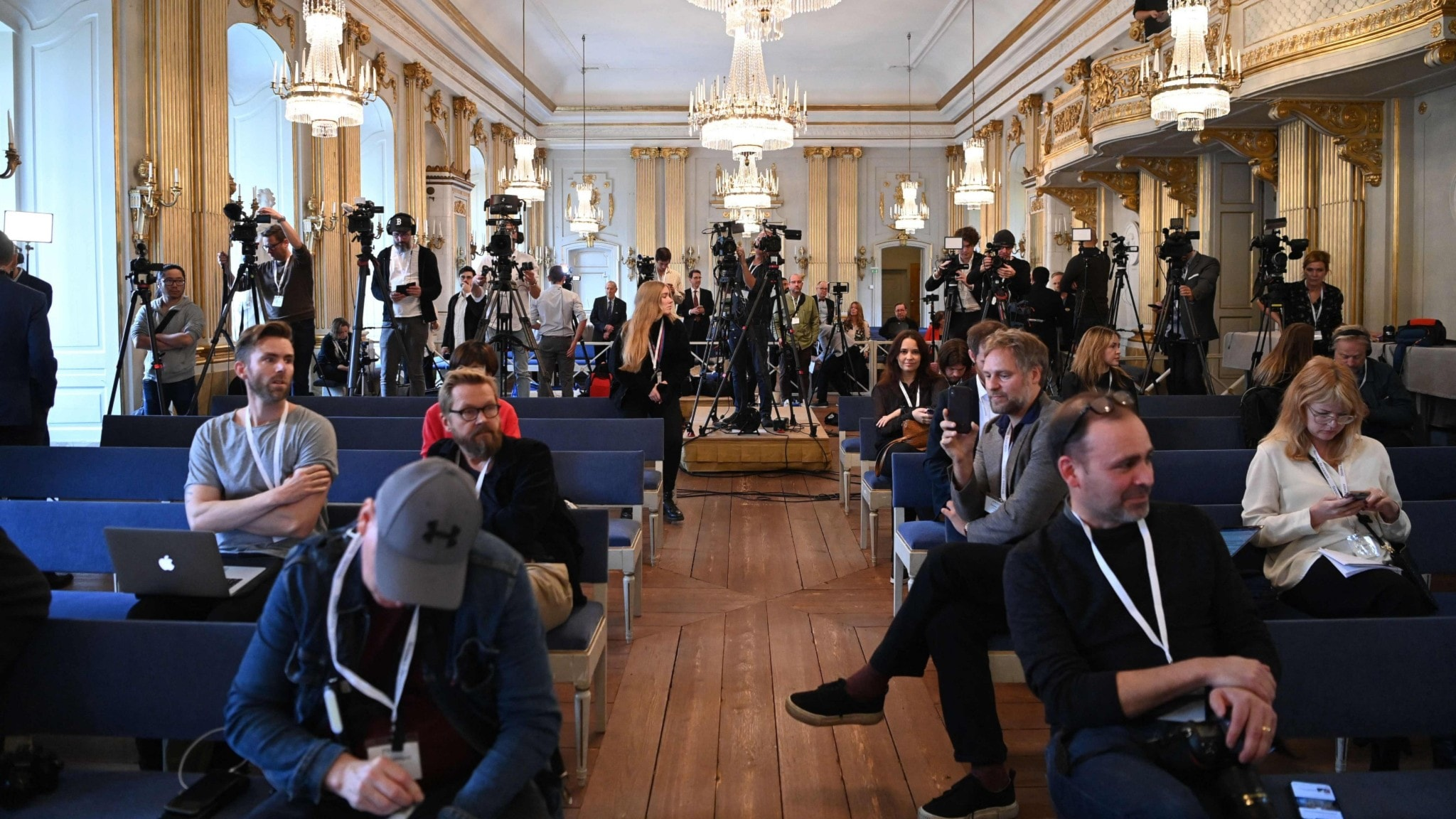 A fancy room with cameras and reporters sitting around.
