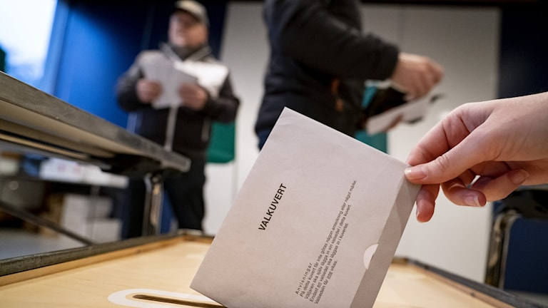 A piece of paper going into a ballot box.