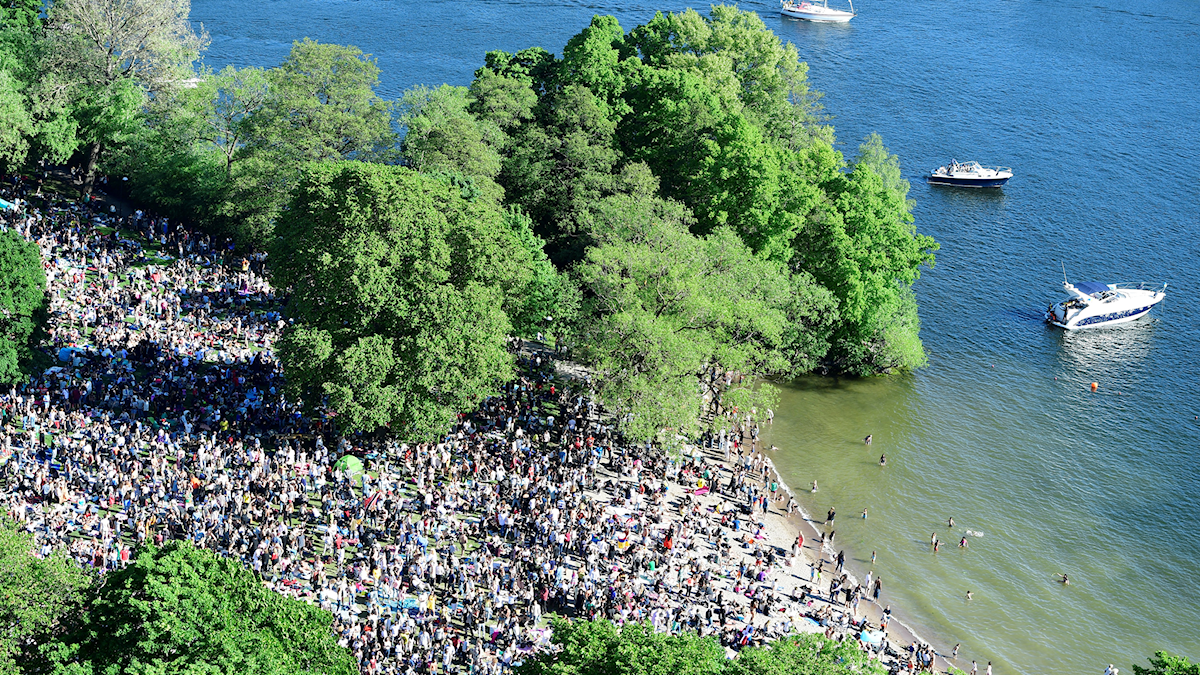 An aerial shot of a festival by a lake