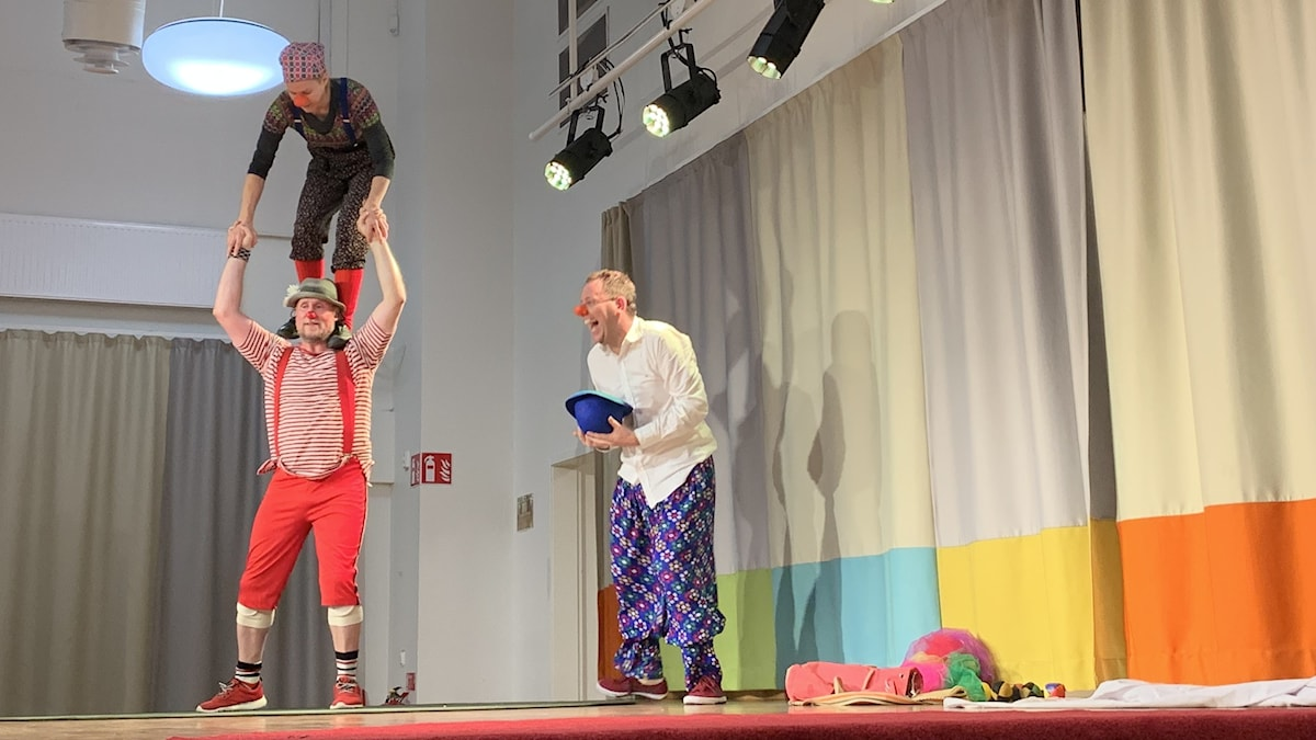 Three clowns on a stage