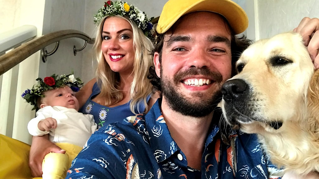 Photo of two adults smiling. One is wearing a yellow baseball cap and patterned shirt and has his hand on a labrador retreiver dog. The other adult is wearing a Midsummer wreath, just like the baby she is holding.