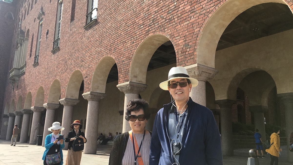 Two people standing in front of a colonnade at Stockholm City Hall