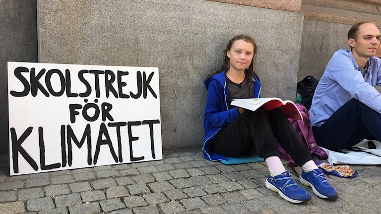 Teenager seated on the ground with a book in her lap. Next to her is propped a placard with hand-painted letters.