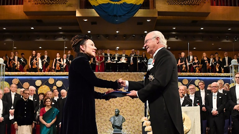 A nobel winner recieving their prize from the Swedish King.