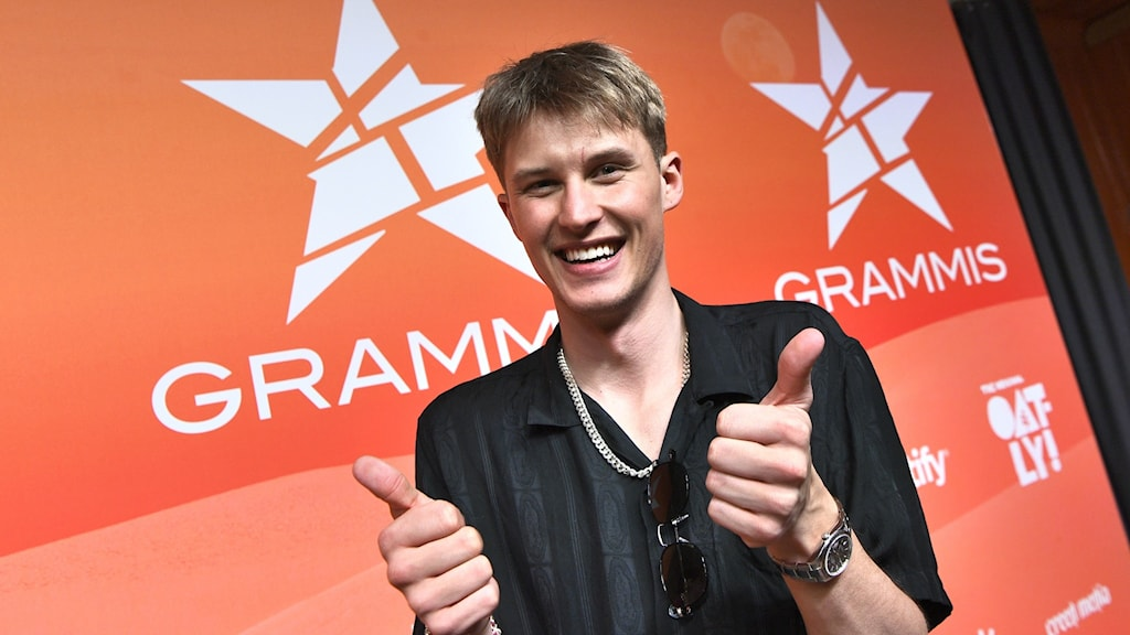 A person showing two thumbs up in front of a screen that says Grammis