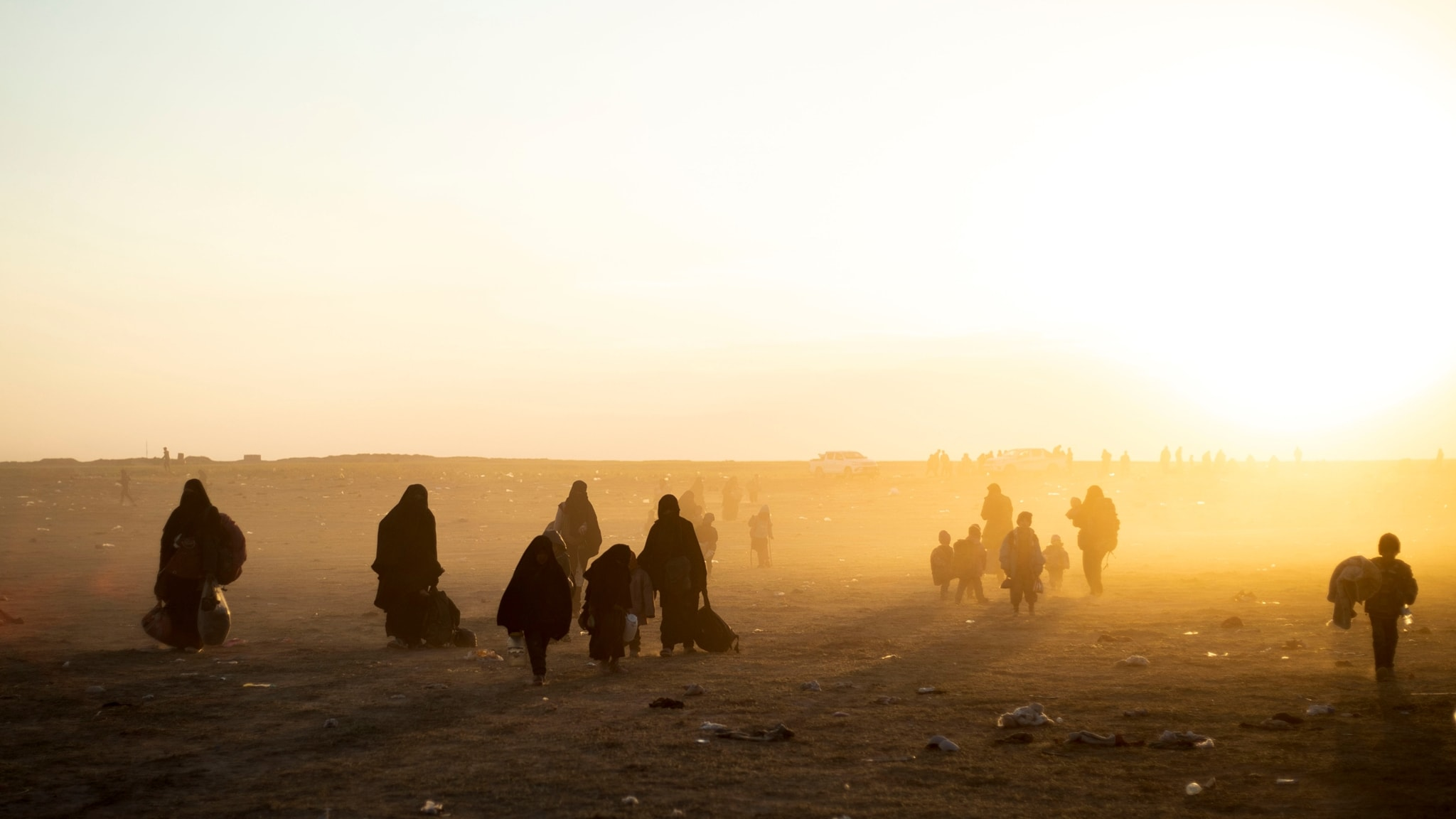 Silhouette of  people carrying bags and wounded through a dry landscape.