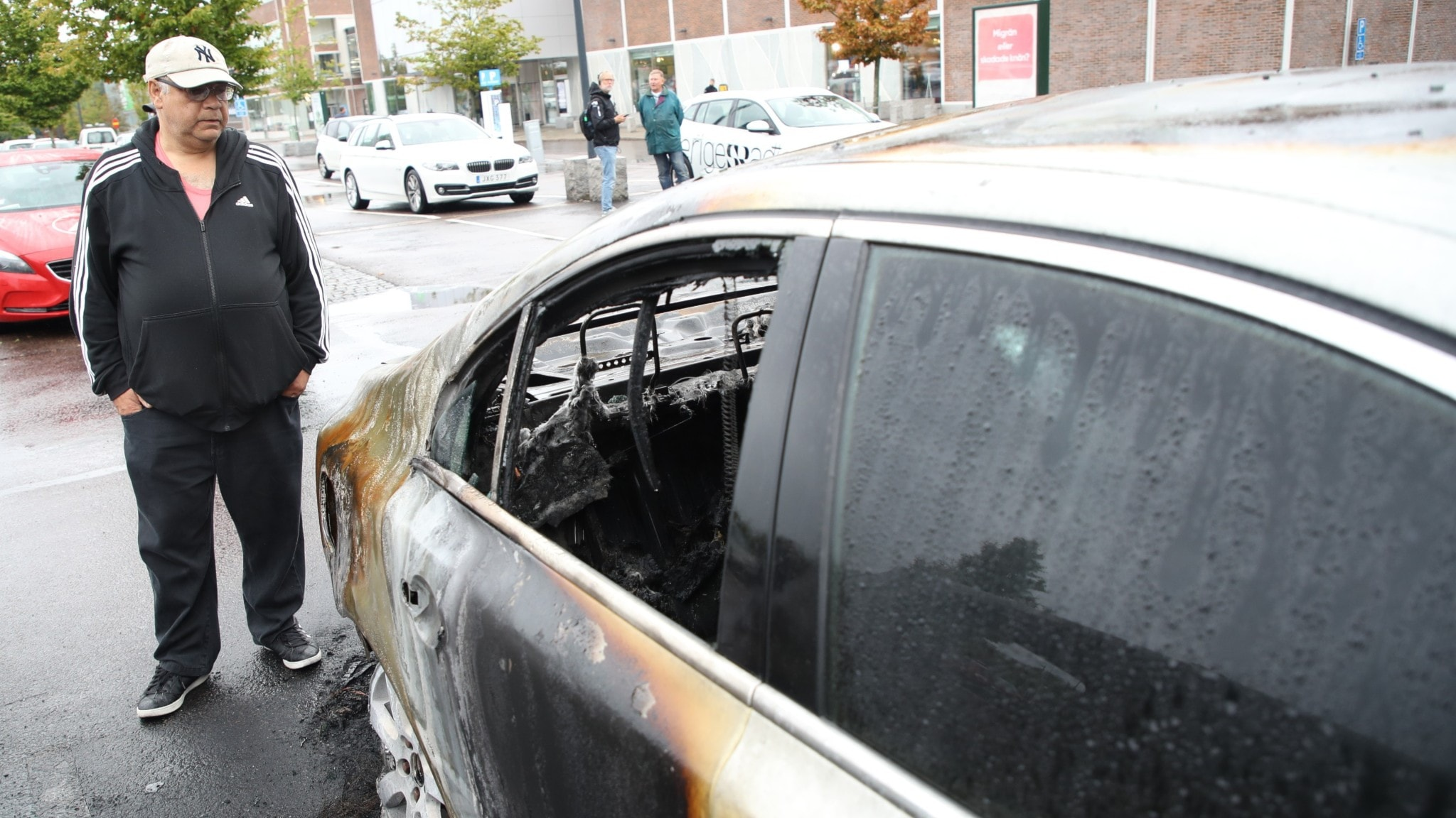 A man standing next to the charred remains of a car.