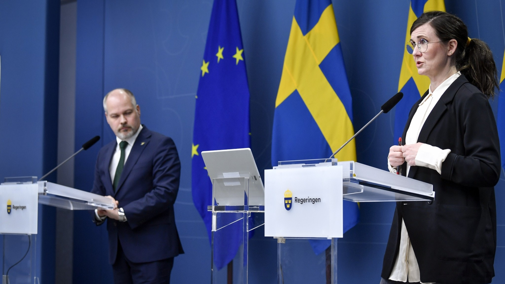 A woman and a man standing apart in front of lecterns.