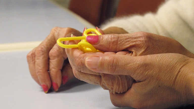 An older patient being helped with a puzzle.