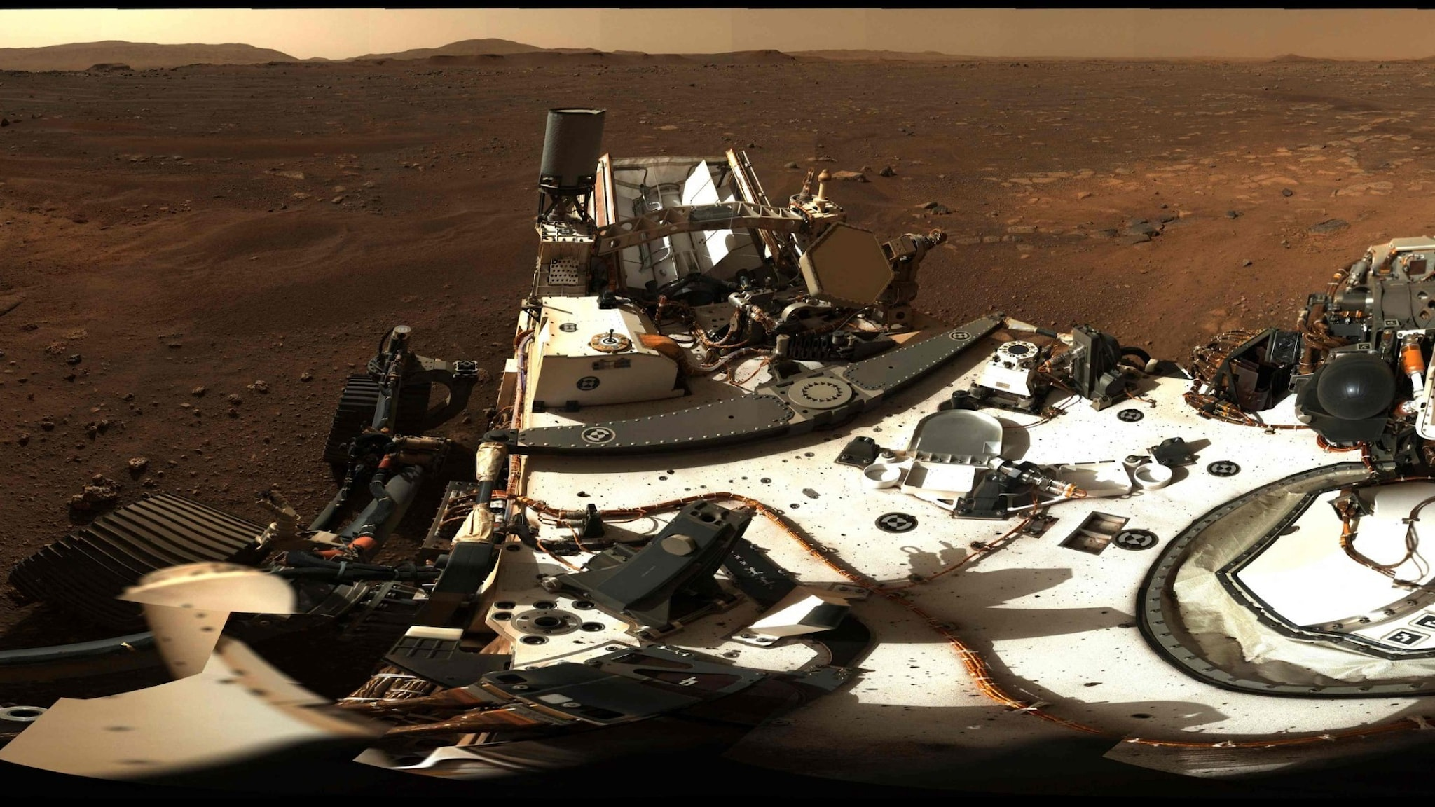 The shiny surface of a rover on a rust-colored ground with light on the horizon.