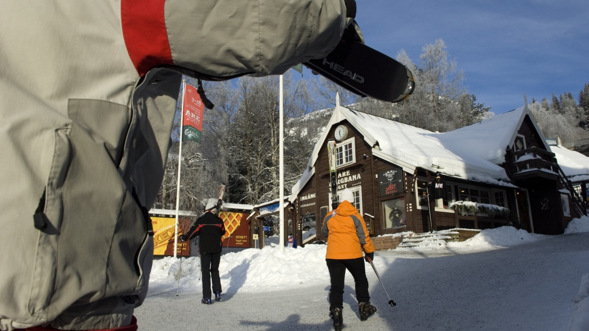 People dressed in skiing gear outdoors on a sunny, snowy day, in front of a building and slope.