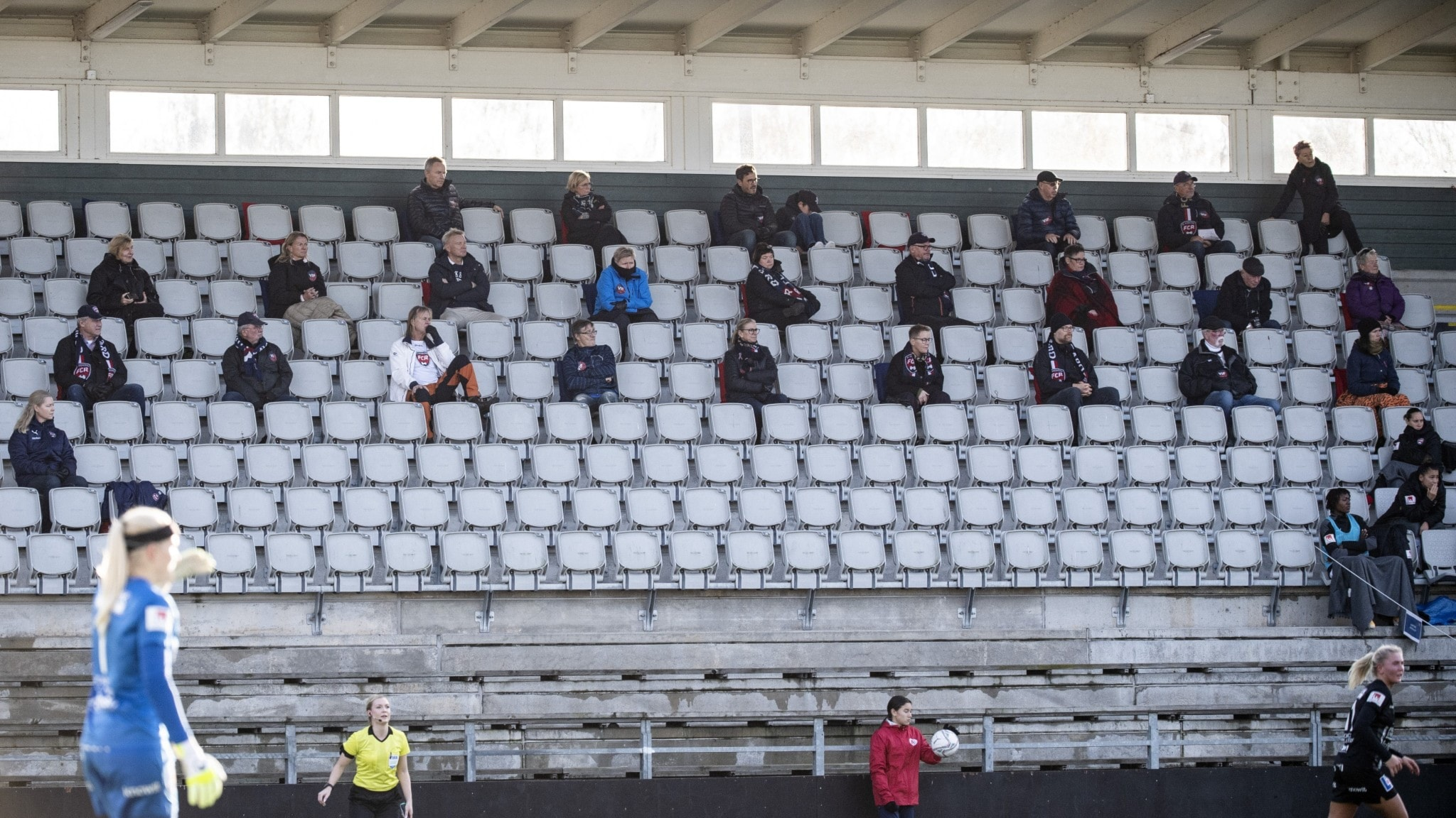 A sports arena stand with people sitting spread out.
