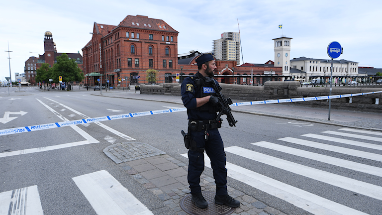 An armed officer standing in a street with a brick building behind him.