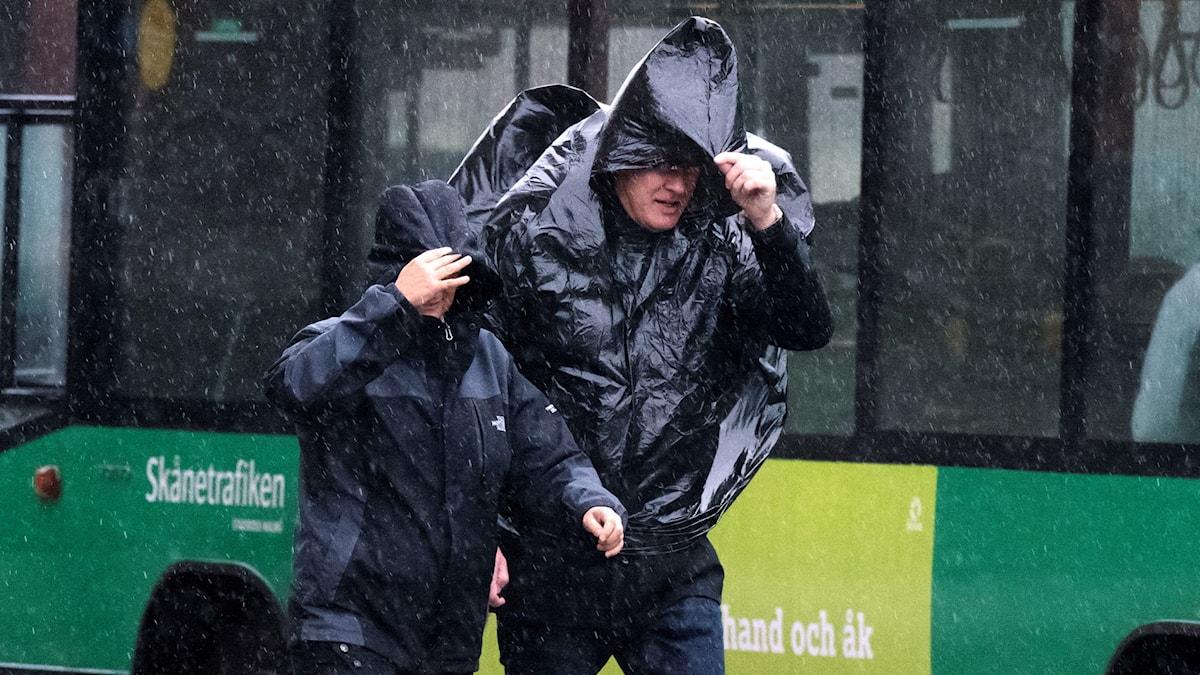 Two men walking through wind and rain.