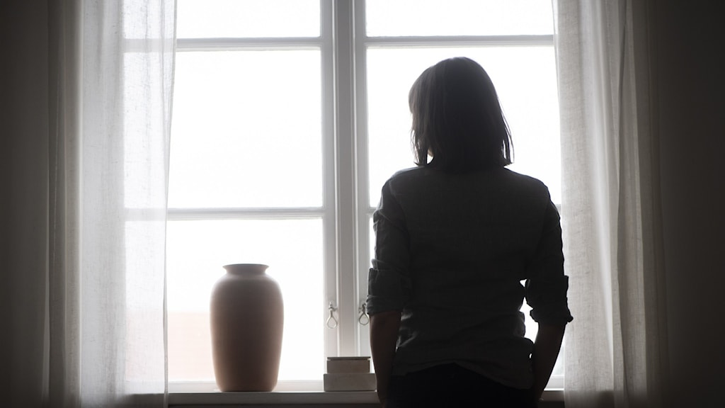 A dark picture of an outline of a person against a bright window.