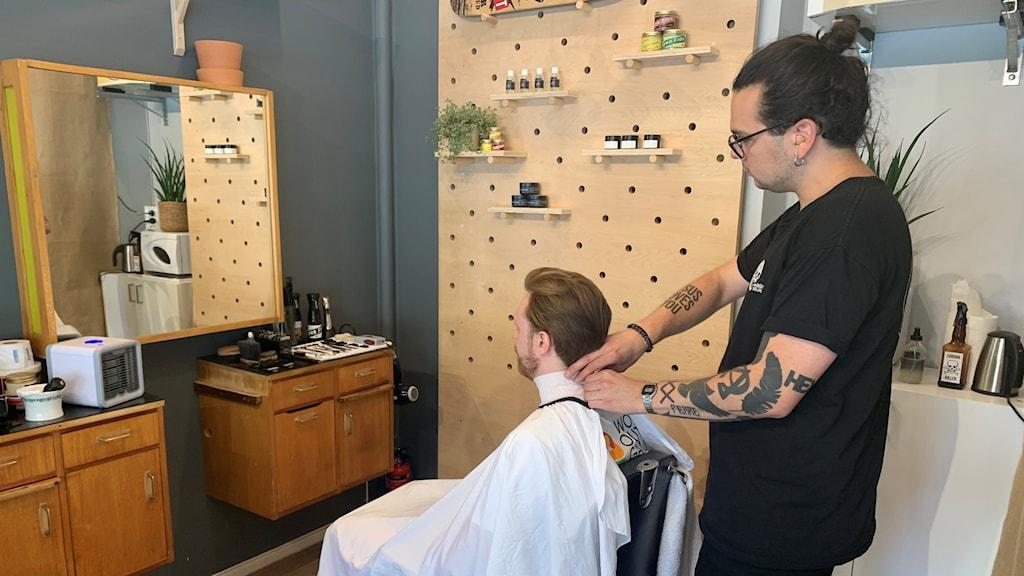 Barber preparing to cut a man's hair.