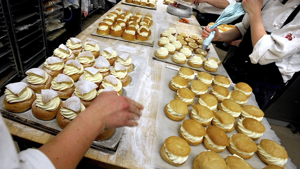 Several trays of semla buns being assembled in a kitchen.
