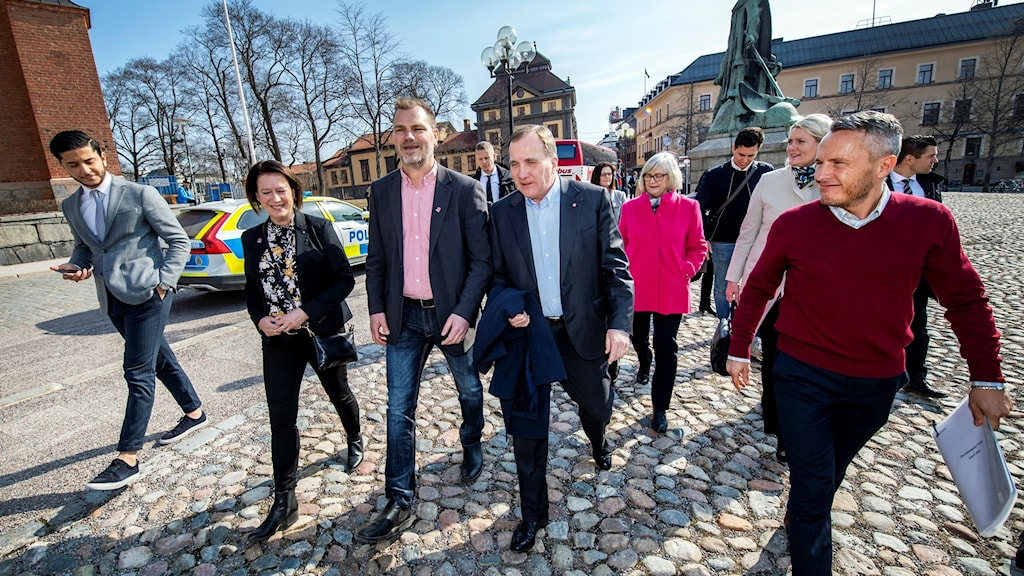 Man walks across a town square, surrounded by party faithfuls.