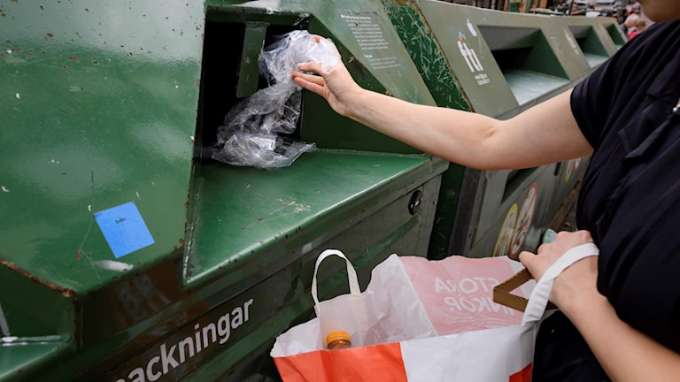 A person throwing away rubbish in a recycling container