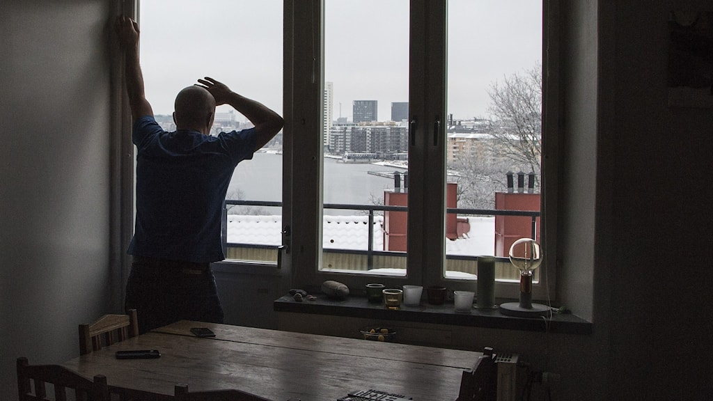 A man standing up, leaning against a window.