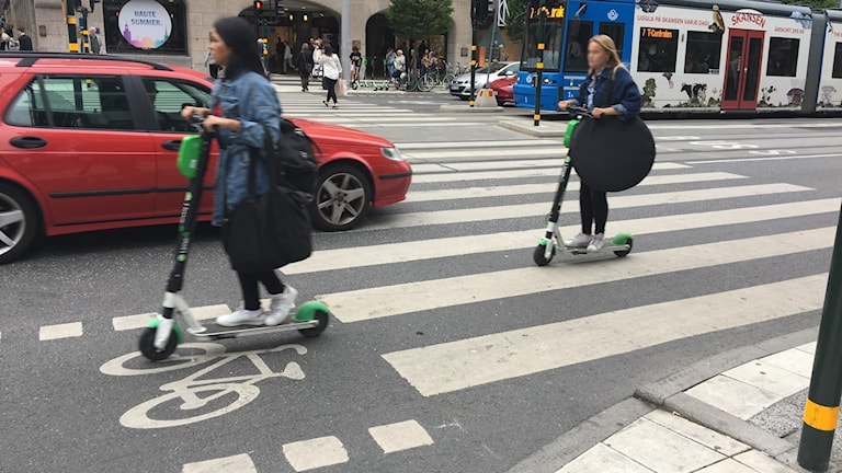 People riding electric scooters in Stockholm traffic