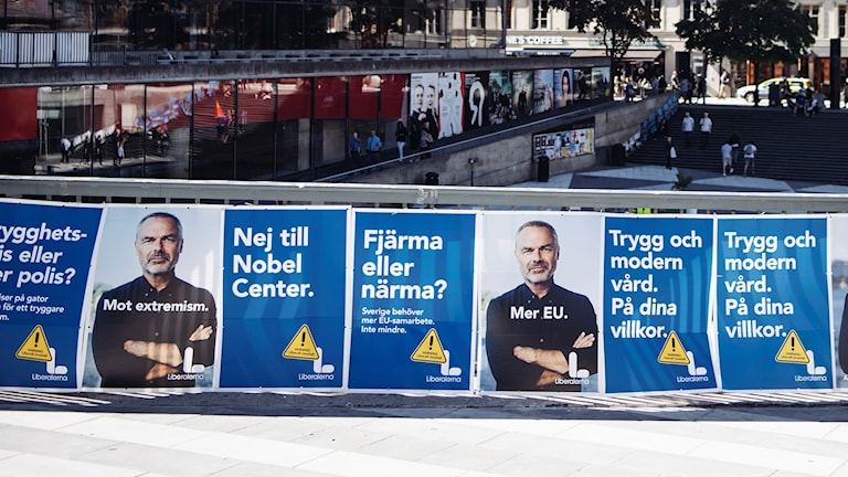 Election posters for the Liberal Party on a fence.