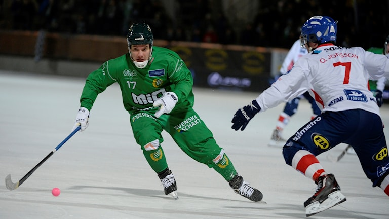Two Swedish bandy players facing off in Stockholm's Zinkensdamm Stadium.
