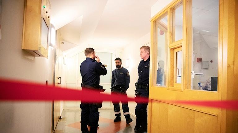 Men standing in a hallway.