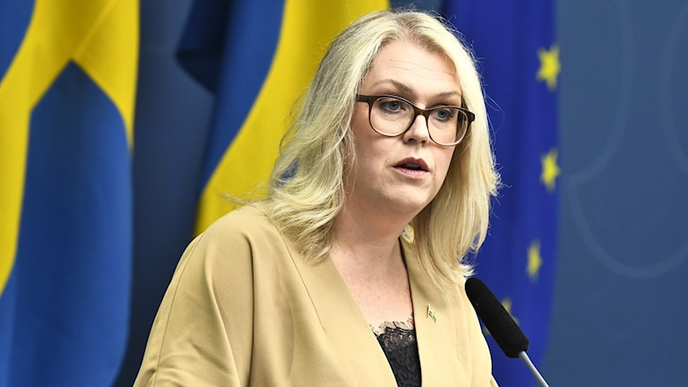 Lena Hallengren at a corona press conference with a Swedish flag behind her.