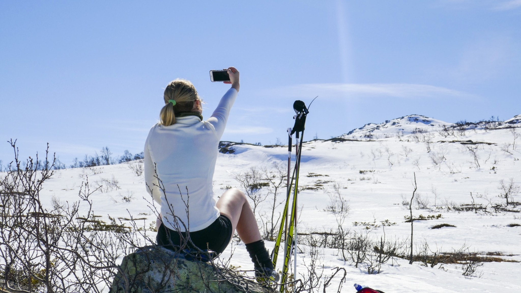 A skiier taking a selfie in the sun