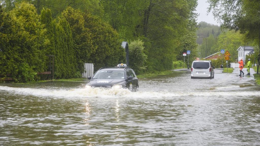 Översvämmad gata efter kraftigt regn. En taxibil kör i vattnet.