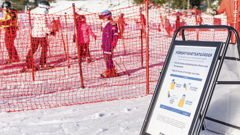 Fencing on a snowy field with skiers in the background and a sandwich board in the foreground.