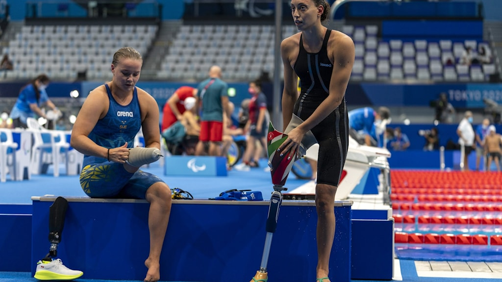 Swimmers with one leg by the side of an olympic pool