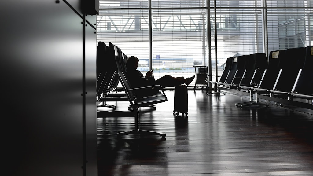 A person waiting for a plane with some luggage.