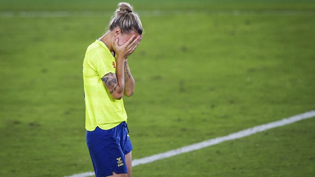 Player Nathalie Björn holds her head in her hands.