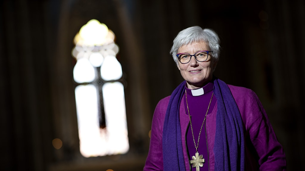 A woman in purple against the background of a church window (Archbishop Antje Jackelén)