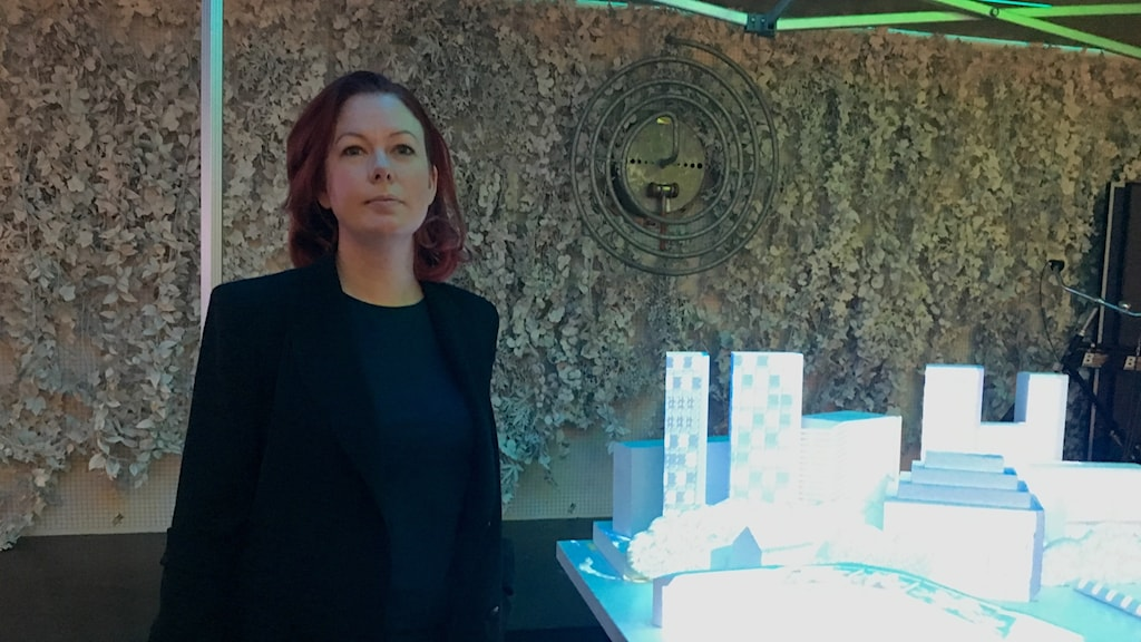 Anya Alenberg stands in front of a lit-up model at the Bahnhof offices in Stockholm.