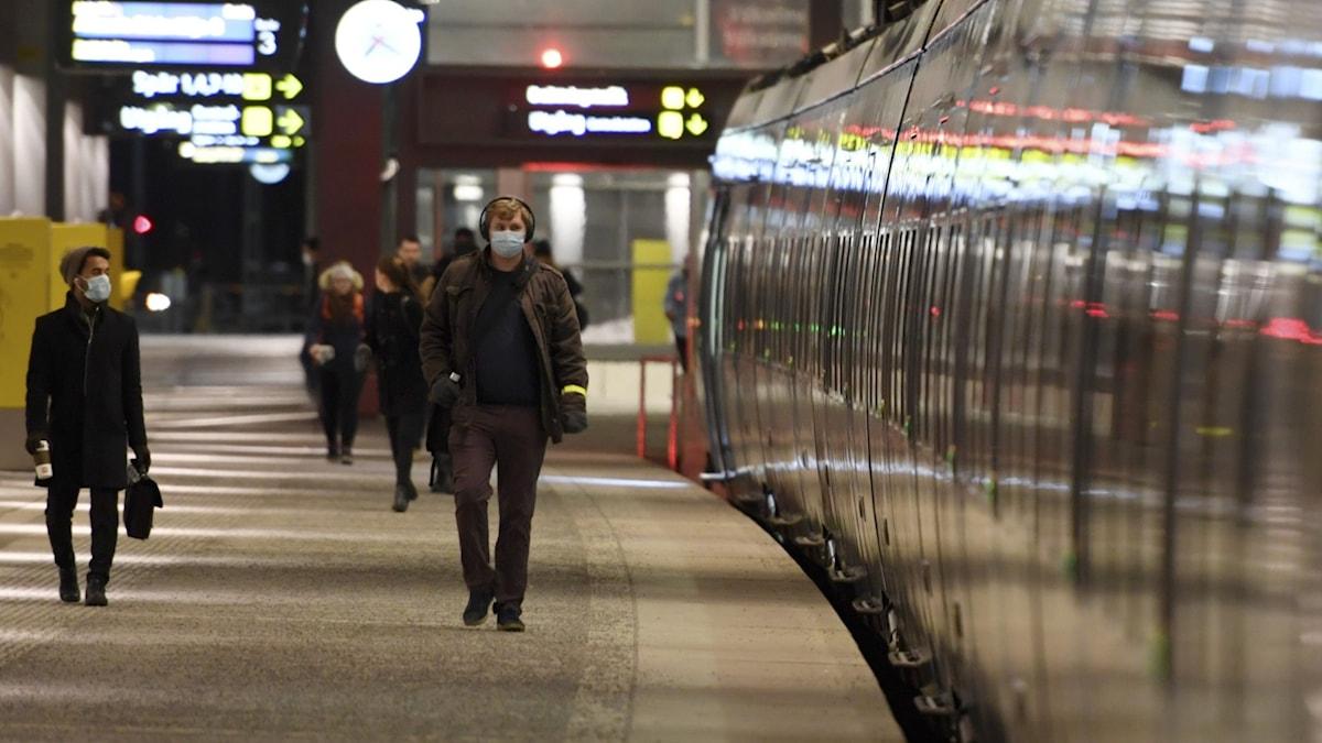 People wearing face masks walk by a train.