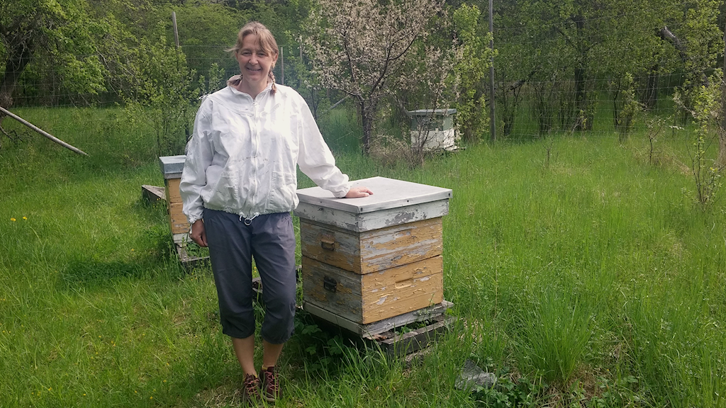Beekeeper Lotta Fabricius Kristiansen standing next to a hive