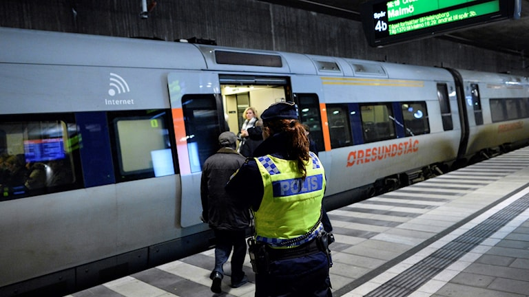 A police officer monitoring a train as part of border control efforts.