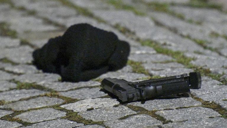 A gun and balaclava on the ground