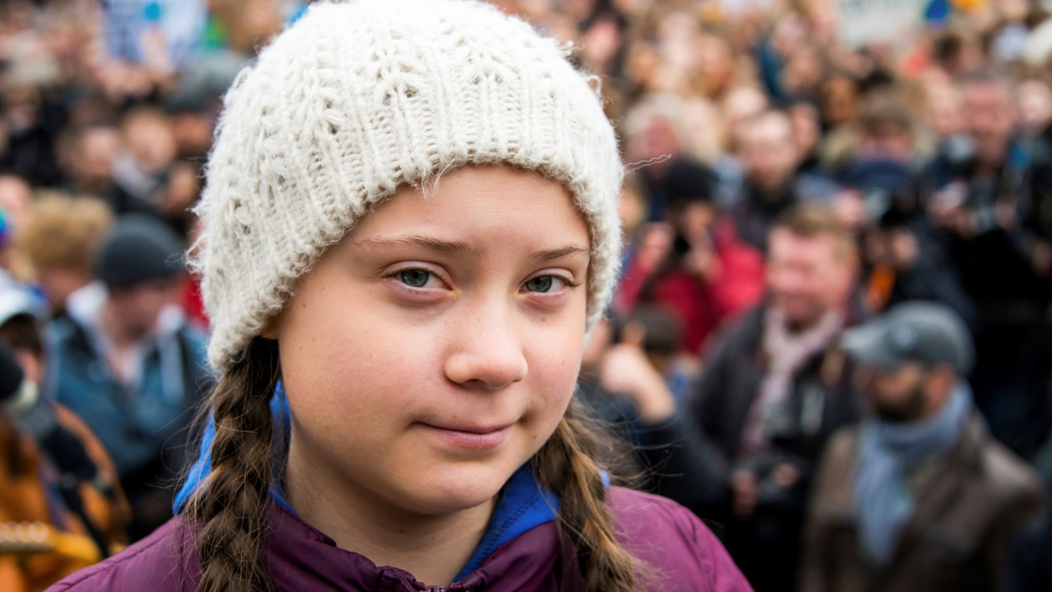 Girl in white bobble hat and braids in front of a big group of people (blurred).