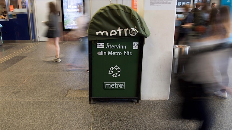 A large green bin in a busy hallway.