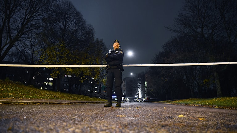 A police officer by police tape at night.