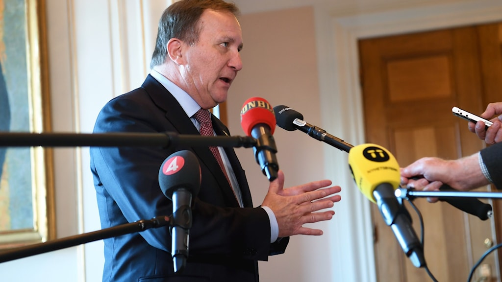 Prime Minister Stefan Löfven standing in front of some microphones.