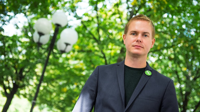 Man with a green pin on his jacket, outdoors.