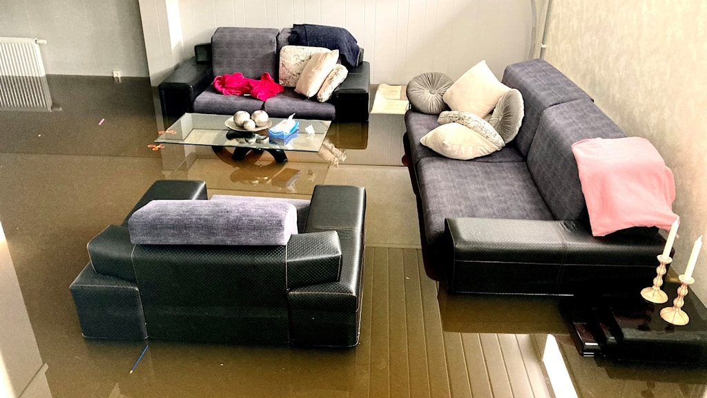 A room with sofas flooded with brown water