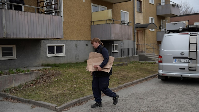 Polce carry material outside an apartment building.